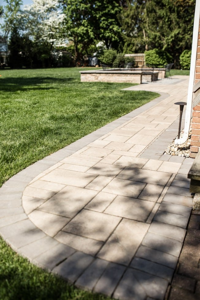 Here is an image of a walkway project we recently tackled in Camp Hill PA. This image showcases a lush lawn surrounding a clean completed project. In the distance, there is a stone patio with a built in fire pit.