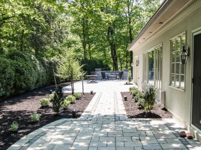 We are outdoor walkway installers that recently tackled this project in Camp Hill PA. This image shows two stone patios connected by a walkway. There are plants on either side of the walkway.