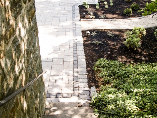 This is a top down view from the top of stairs showcasing one of the outdoor walkways and stone patio installation projects we recently completed as contractors in the Camp Hill PA area. This image shows two different styles of walkway connecting to a stone patio.
