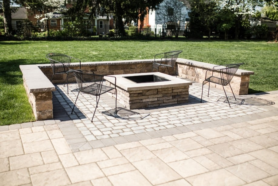 Here is another angle of the fire pit we installed during our stone patio installation project in camp hill PA. This image shows the patio, lush grass, and a black fence that lines the backyard.
