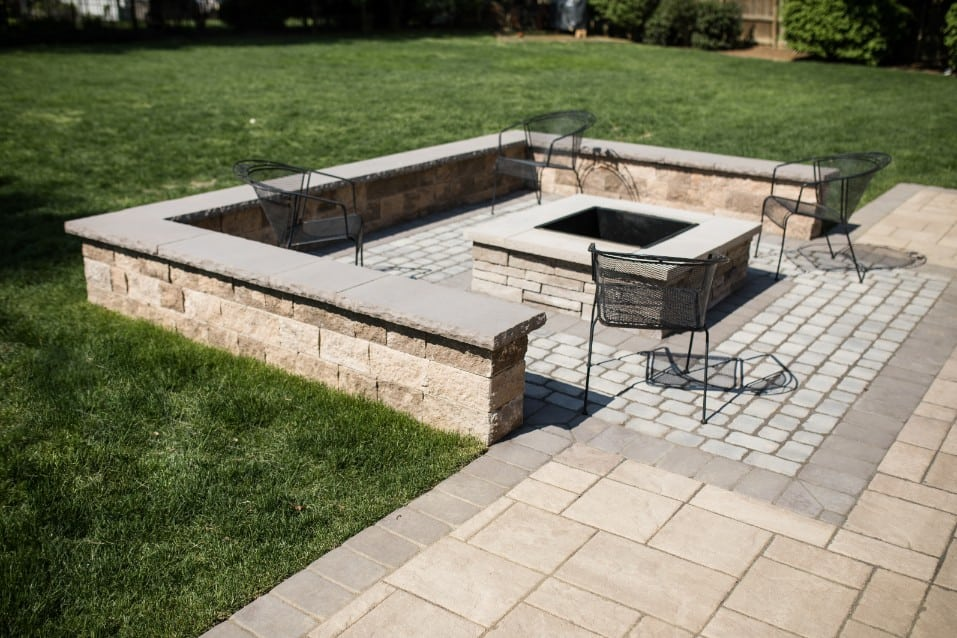 Check out this fire pit we installed during this stone patio installation project in camp hill PA. The weather was just too good for us! This image shows 4 metal chairs surrounding the fire pit.