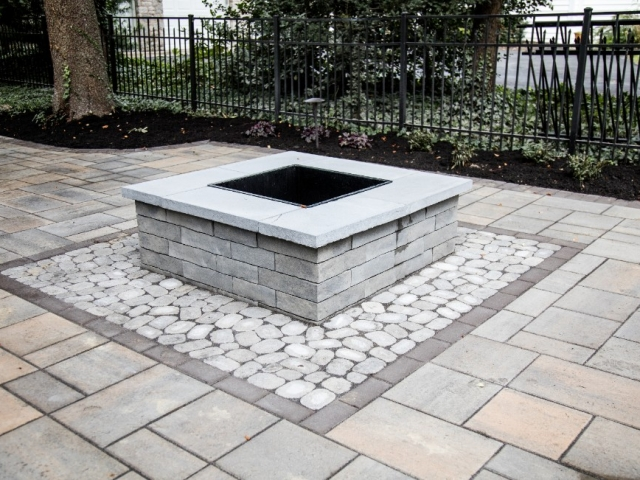 This image shows a large stone patio installation project recently tackled in camp hill pa. The installation also led us to install a square fire put. There is a black fence that runs along one side of the patio.
