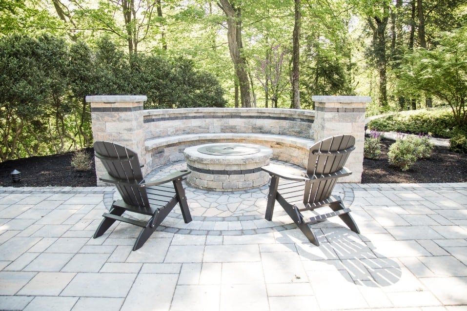 Check out this beautiful stone patio installation project we recently completed. We are one of the top companies in camp hill PA for all things patio. This image also shows a fire pit on the patio with lawn chairs surrounding it, ready for enjoyment.