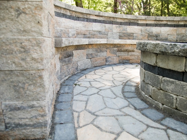 Check out this close up shot of the side of a fire pit we completed during a stone patio installation project. This image shows numerous styles and colors of stone that make up the patio and the fire pit. We are one of the stop patio installation companies in Camp Hill PA.