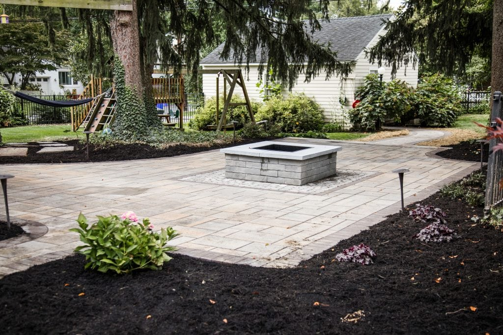 Here is a wide view of a project our stone patio installation contractors completed in Harrisburg PA. There is freshly planted plants with mulch.