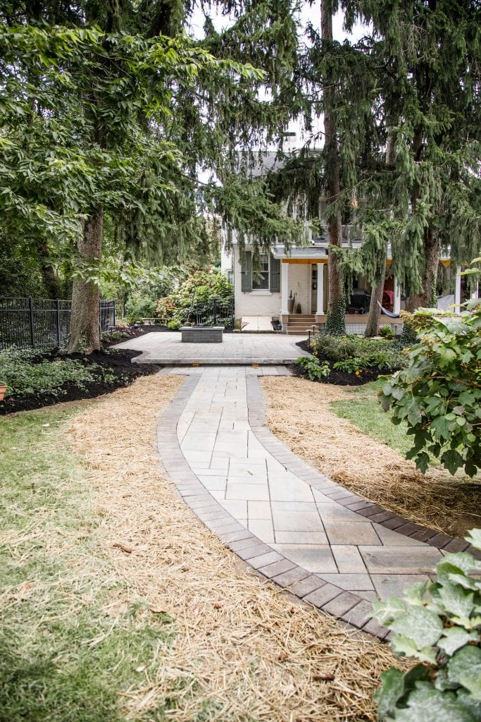 Here is a walkway installation project we completed in Harrisburg PA. THis image shows a curved walkway going to a stone patio with a fireplace.