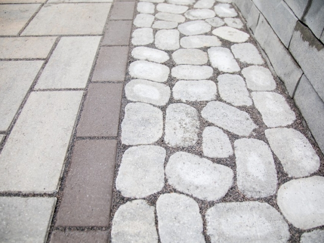 Here is a close up shot of one of the patios we laid down in camp hill pa. This image shows a multitude of colored rocks as well as patterns and shapes. Colors include: gray, red, and tan.